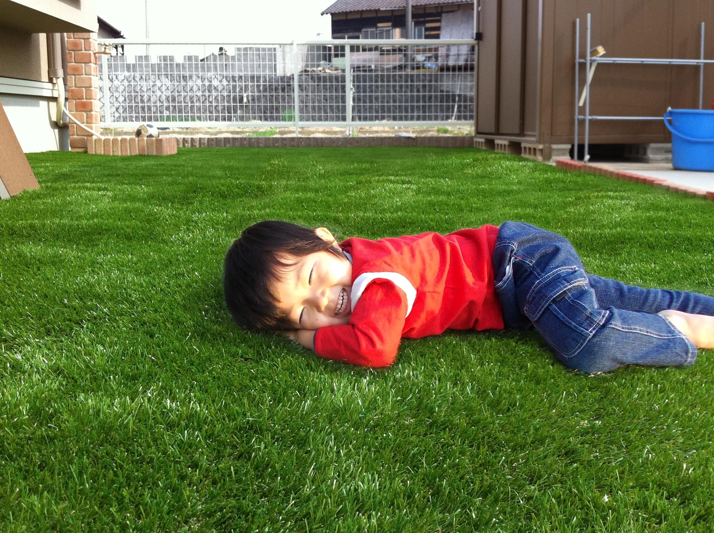 人工芝で寝転がる男の子
